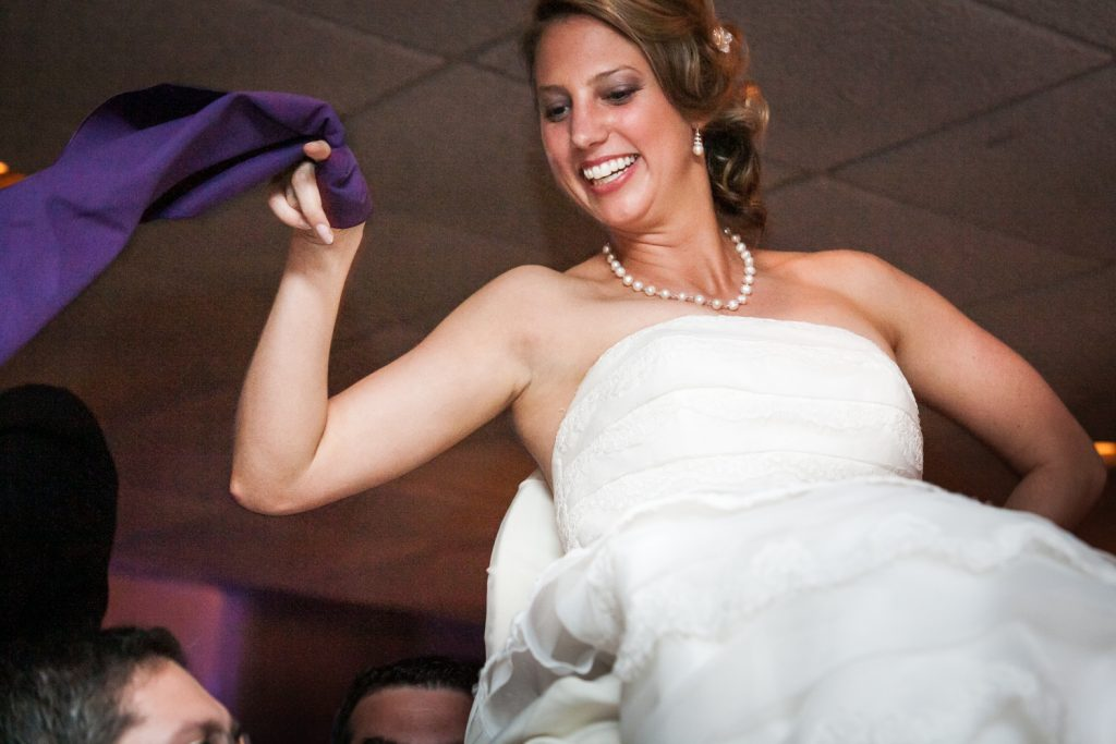 Bride lifted on chair during hora at a Davenport Mansion wedding