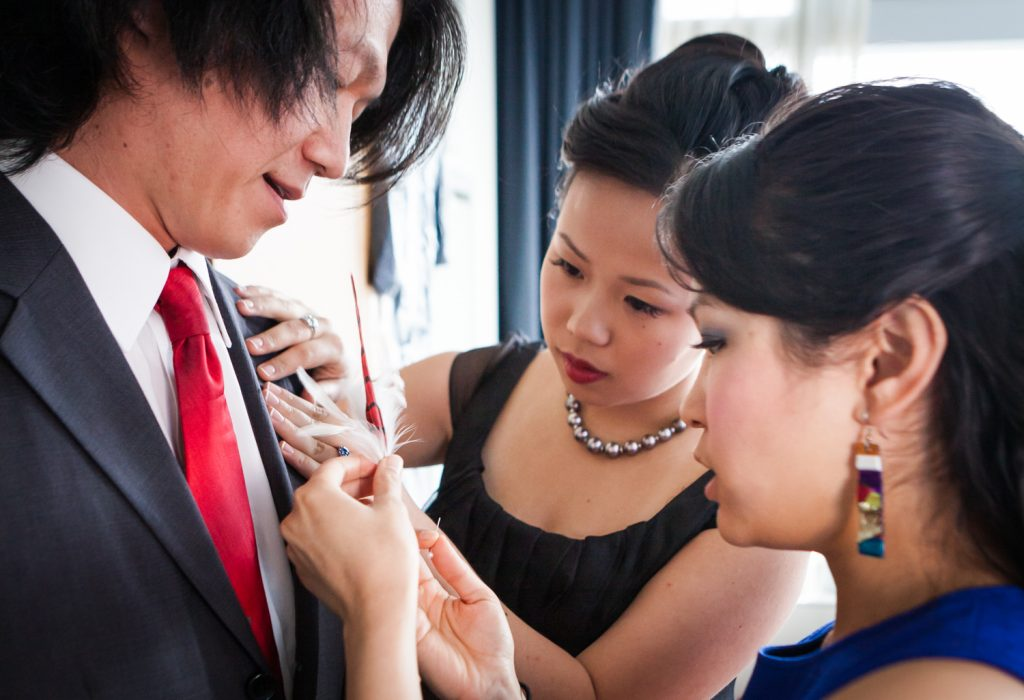 Two women putting feather boutonniere on groomsman