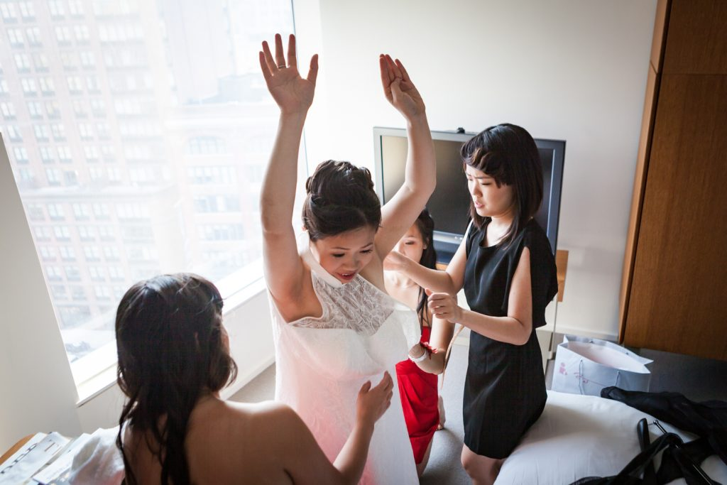 Bridesmaids helping bride get into her dress at a Merchant's House Museum wedding