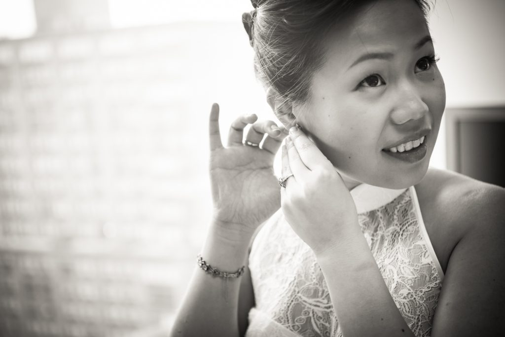 Black and white photo of bride putting in earring