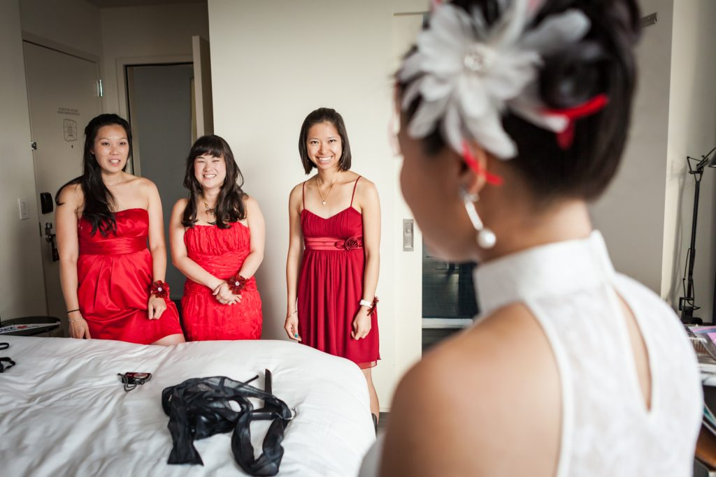 Three bridesmaids wearing red dresses looking at bride at a Merchant's House Museum wedding