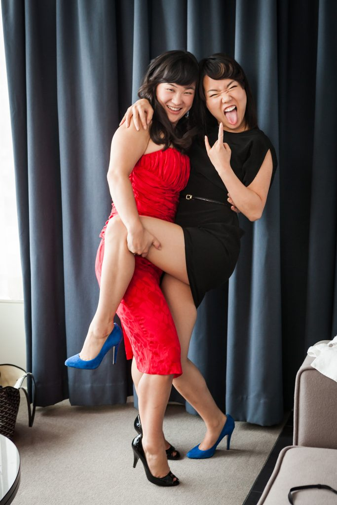 Two bridesmaids hugging and showing devil sign