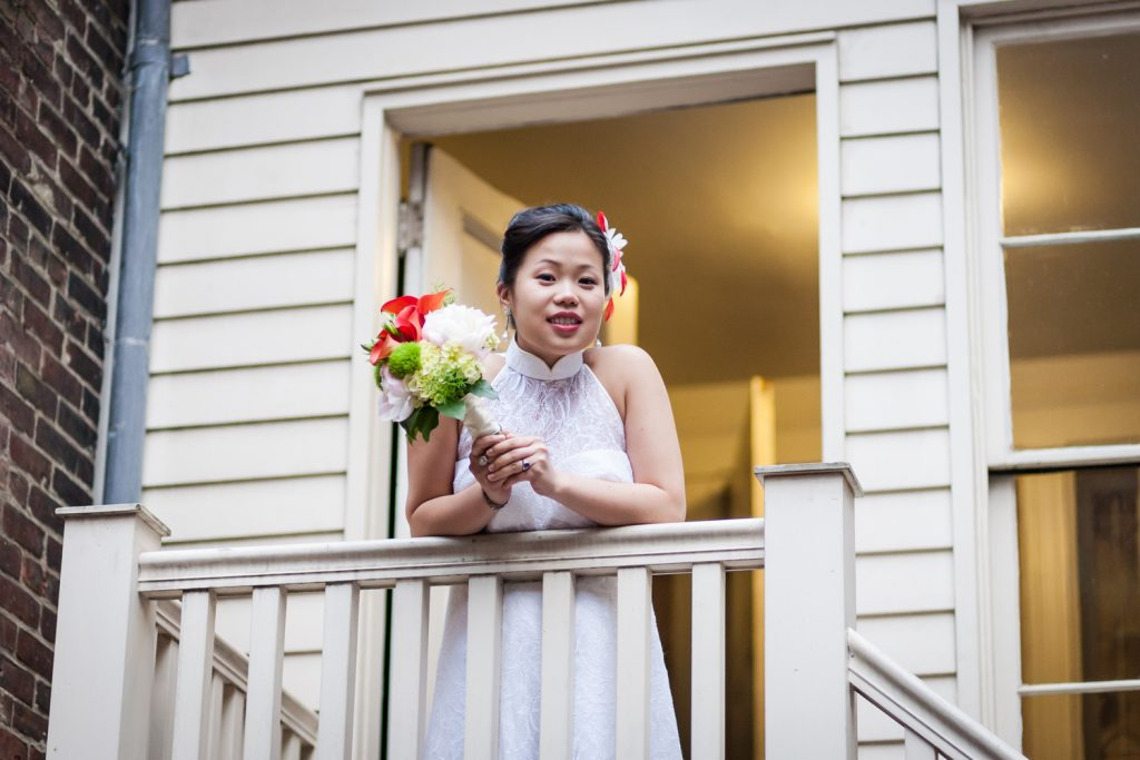 Bride with bouquet leaning on staircase railing at a Merchant's House Museum wedding