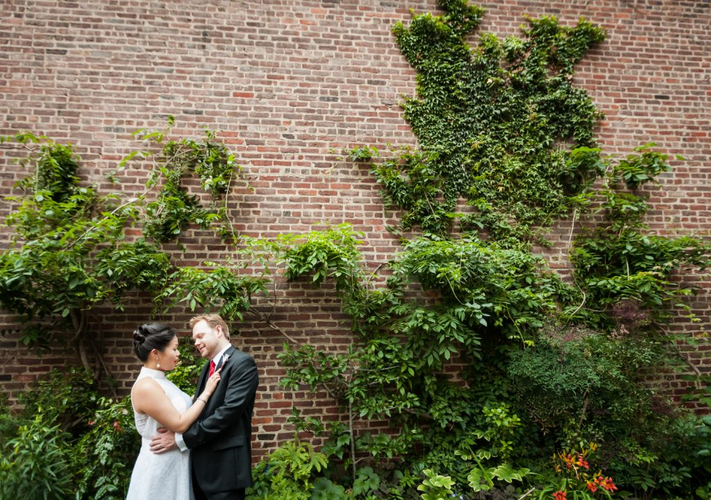 Bride and groom hugging in garden patio at a Merchant's House Museum wedding