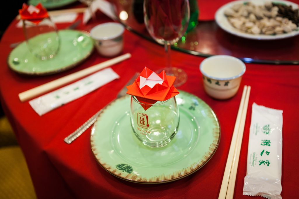 Table setting with green plate and origami at a Congee Village wedding reception