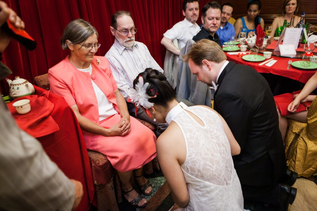 Bride and groom bowing to parents during tea ceremony at a Congee Village wedding reception