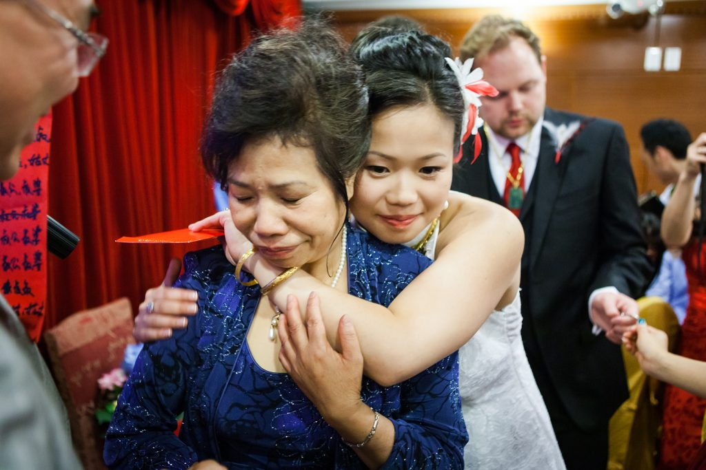 Bride hugging mother during fujisan gold ceremony at Congee Village wedding reception