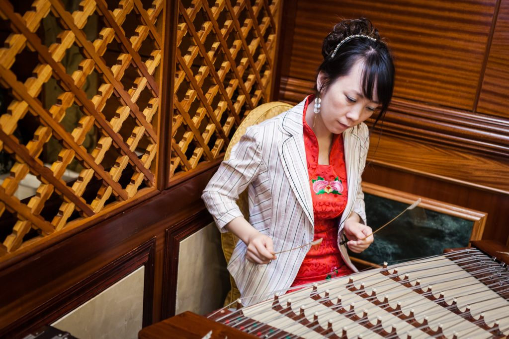 Woman playing musical instrument at a Congee Village wedding reception