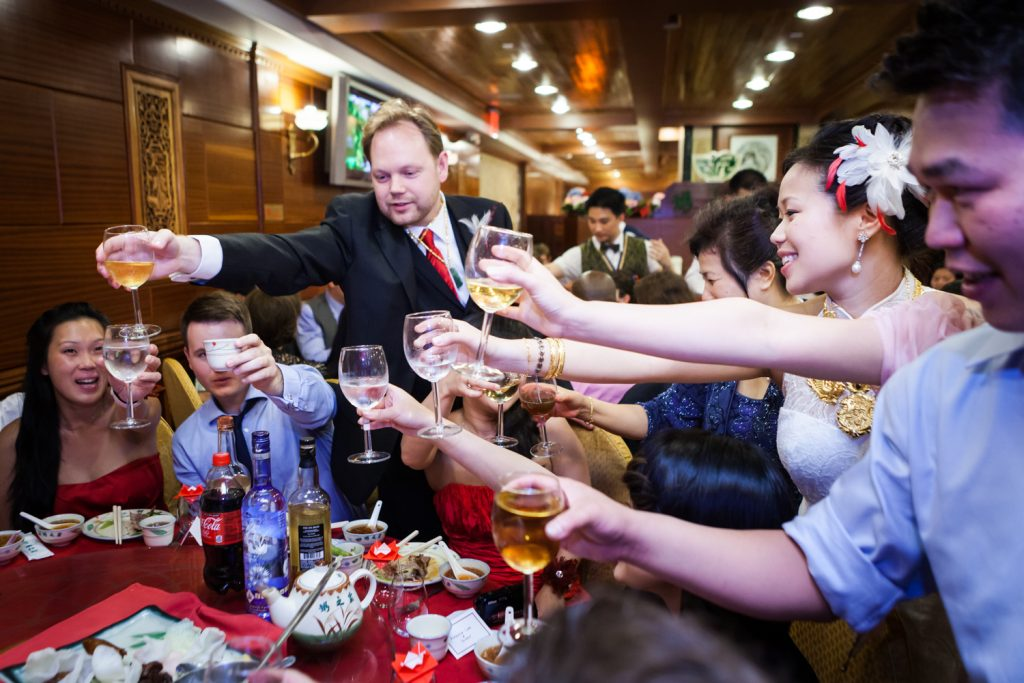 Guests toasting glasses with bride and groom at a Congee Village wedding reception
