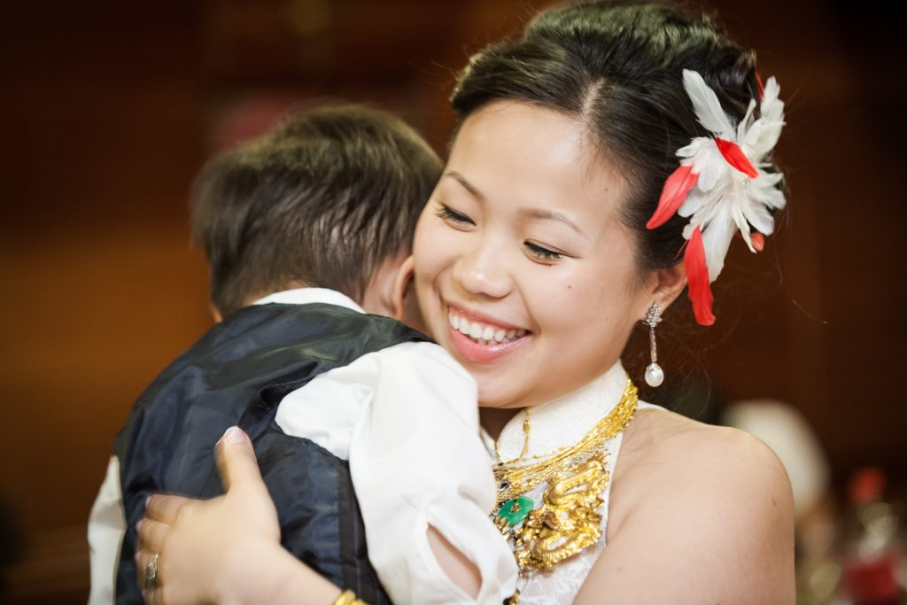 Bride hugging little boy at a Congee Village wedding reception