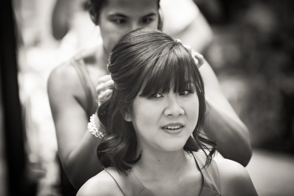Black and white photo of bride looking in mirror while getting hair done