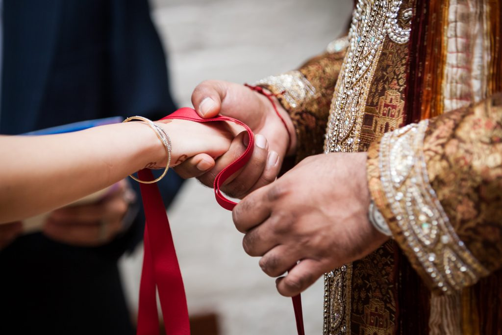 Close up on groom tying bride's hand with red ribbon during ceremony