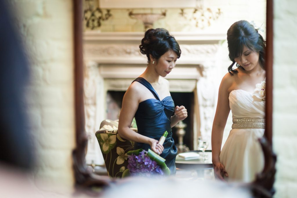 Bride and maid of honor reflected in mirror at an Alger House wedding