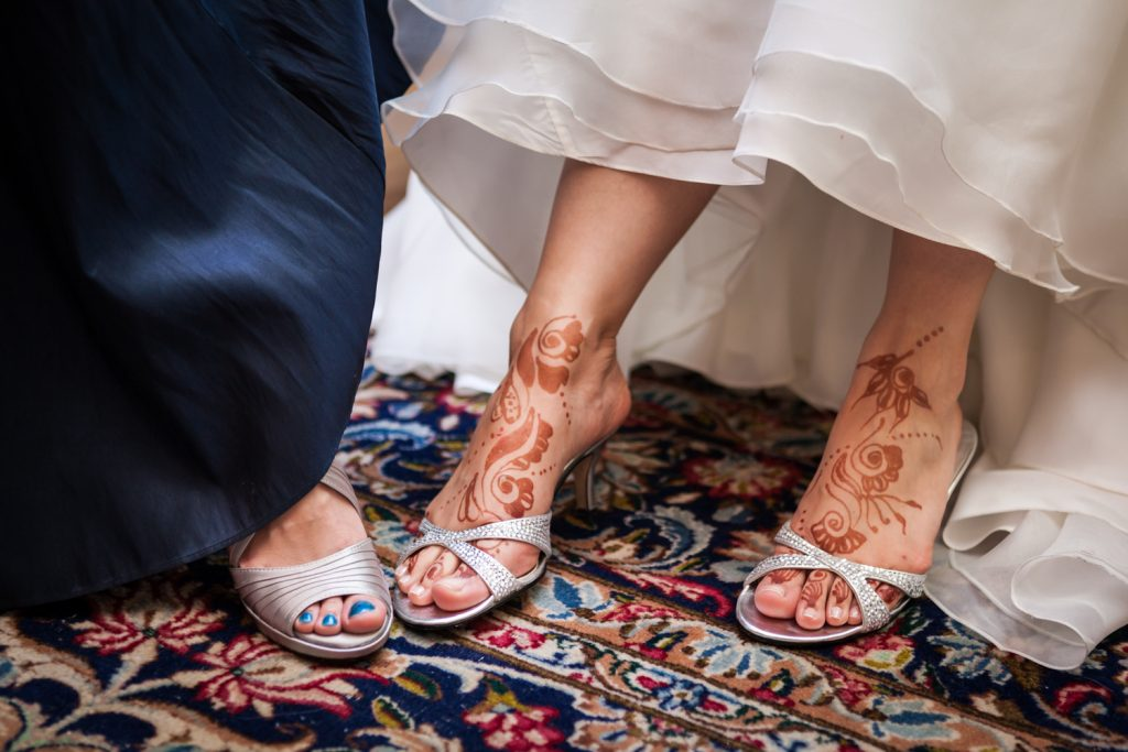 Close up on bride and maid of honor's feet with henna writing