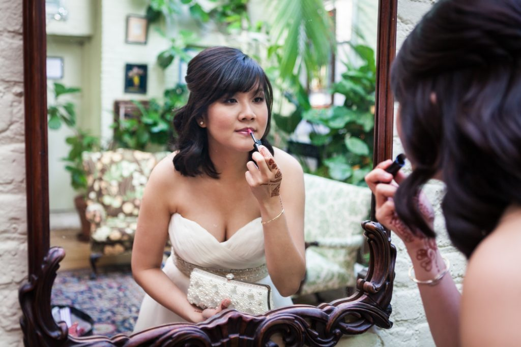 Bride looking in mirror as she puts on lipstick at an Alger House wedding