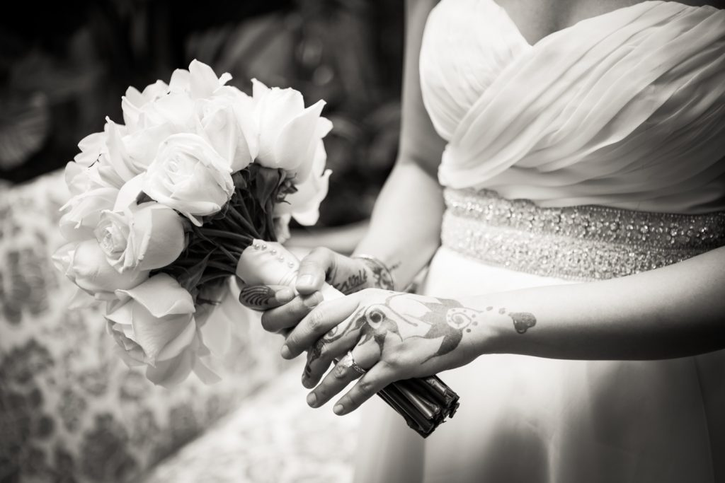 Black and white close up of bride with henna on hands holding bouquet