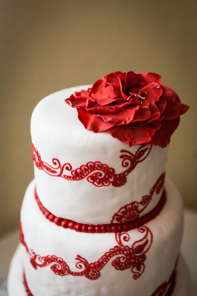 Wedding cake with red filigree icing and red flower on top