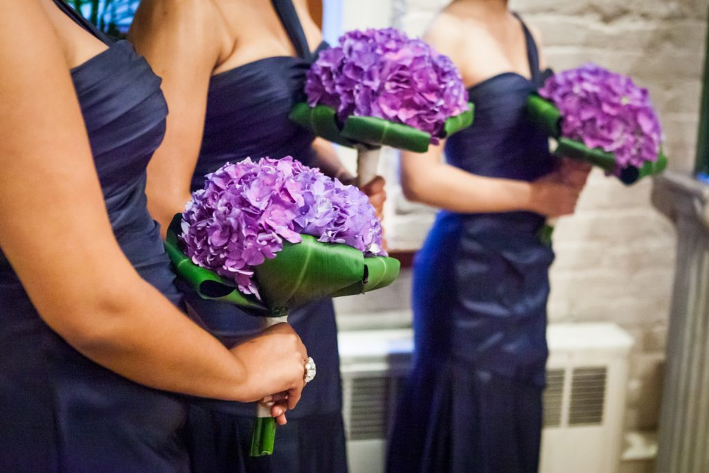Close up on bridesmaids holding giant purple hydrangea bouquets