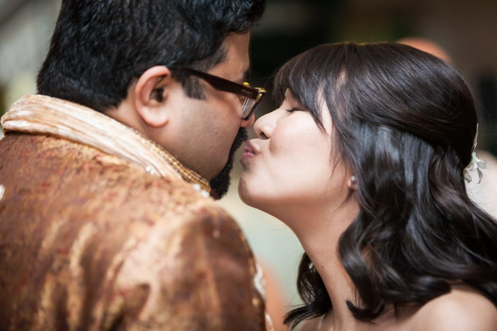 Close up of bride kissing groom on the cheek