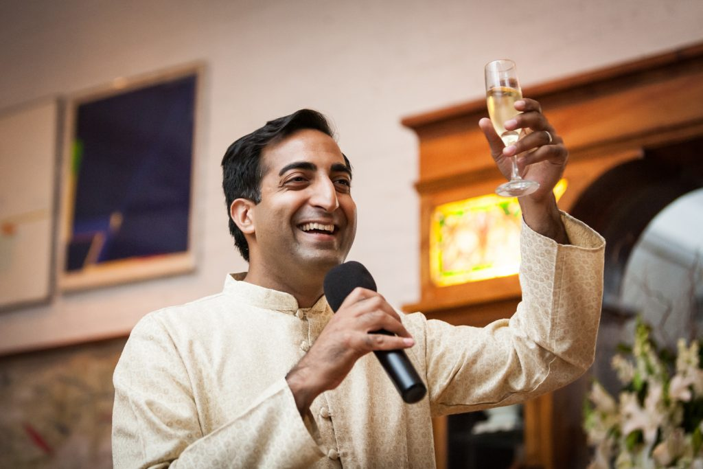 Best man wearing Indian attire holding up a champagne glass during speech