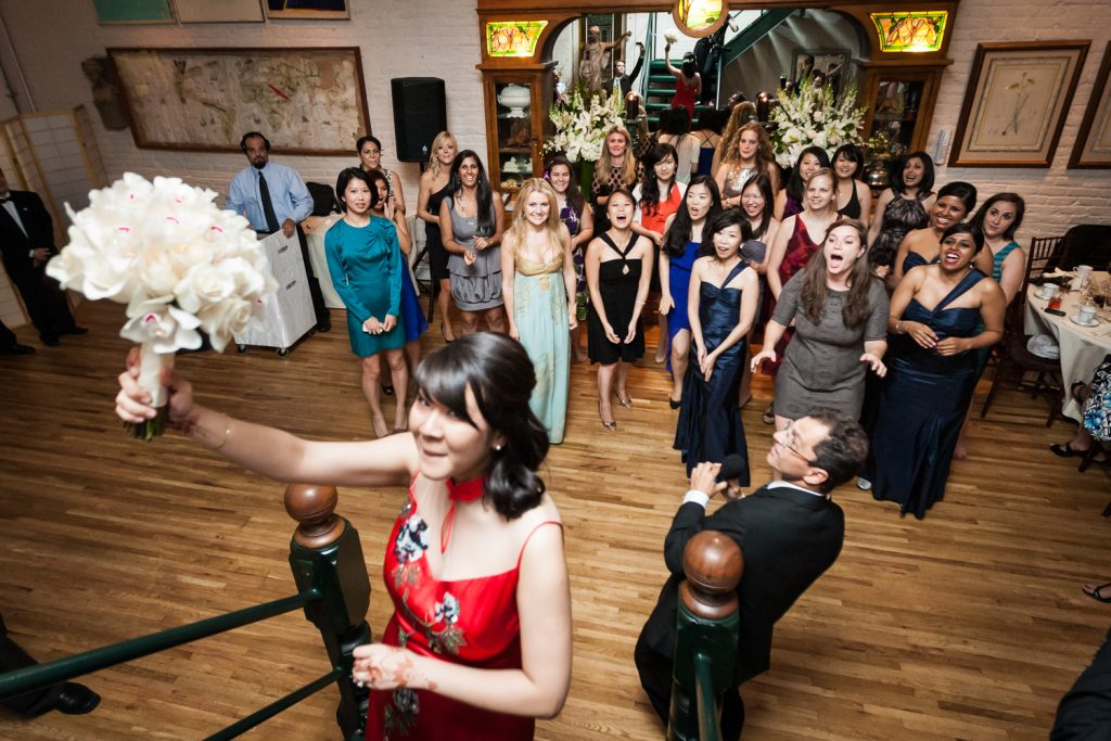 Bride about to throw bouquet to crowd of women at an Alger House wedding