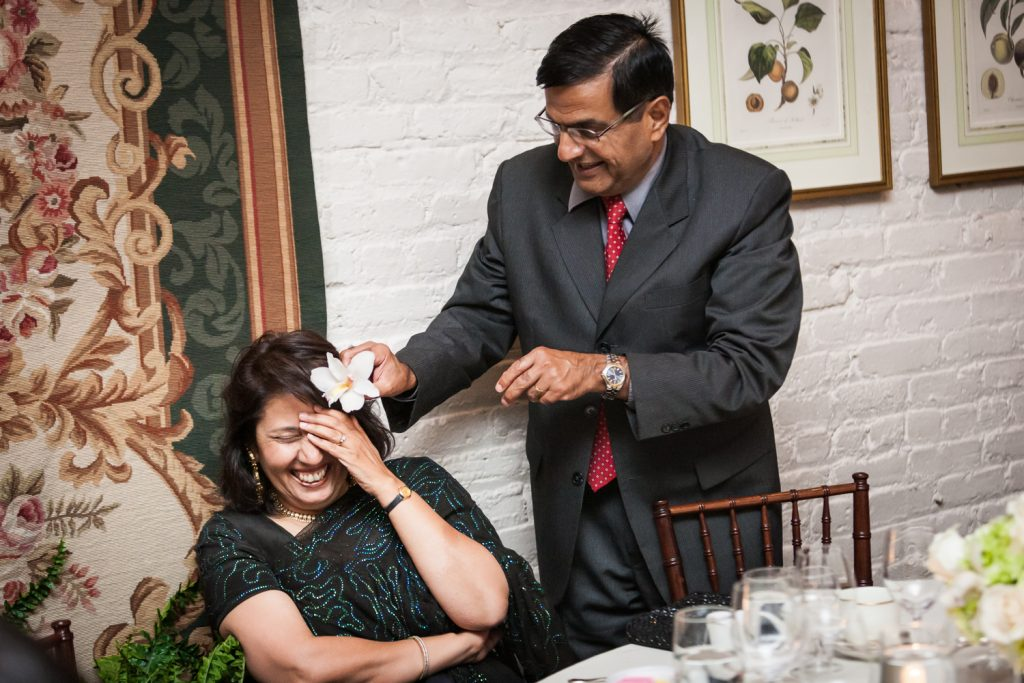 Man putting flower in woman's hair at an Alger House wedding