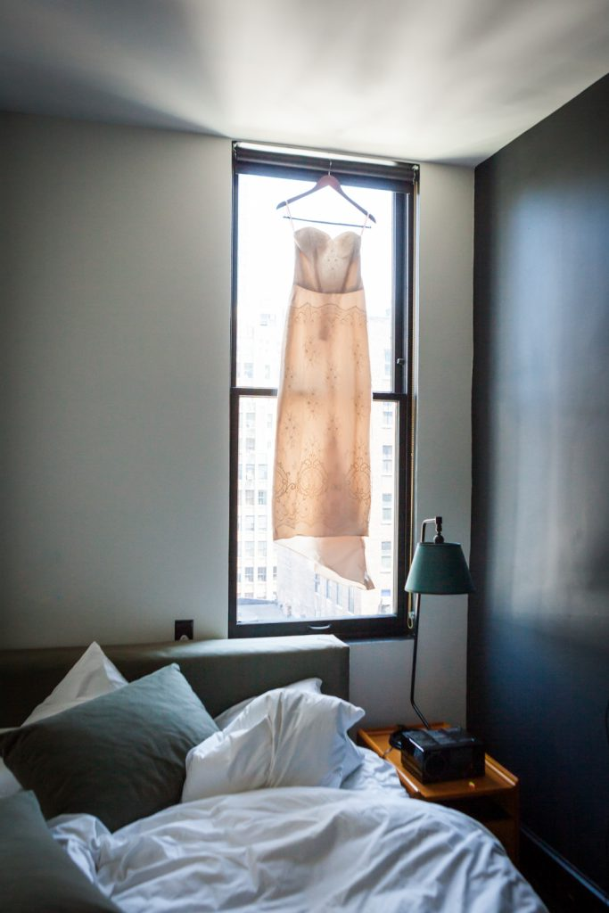 Wedding dress hanging in window of Ace Hotel room