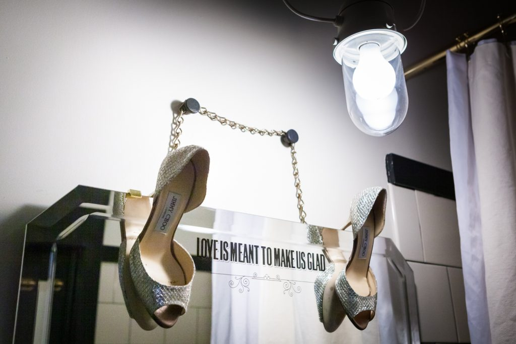 Silver high heels hanging on mirror of Ace Hotel bathroom