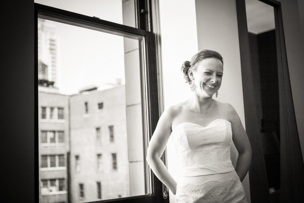 Black and white photo of bride in front of window