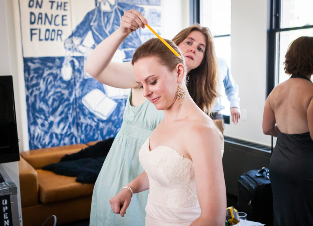 Woman smoothing hair of bride in hotel room
