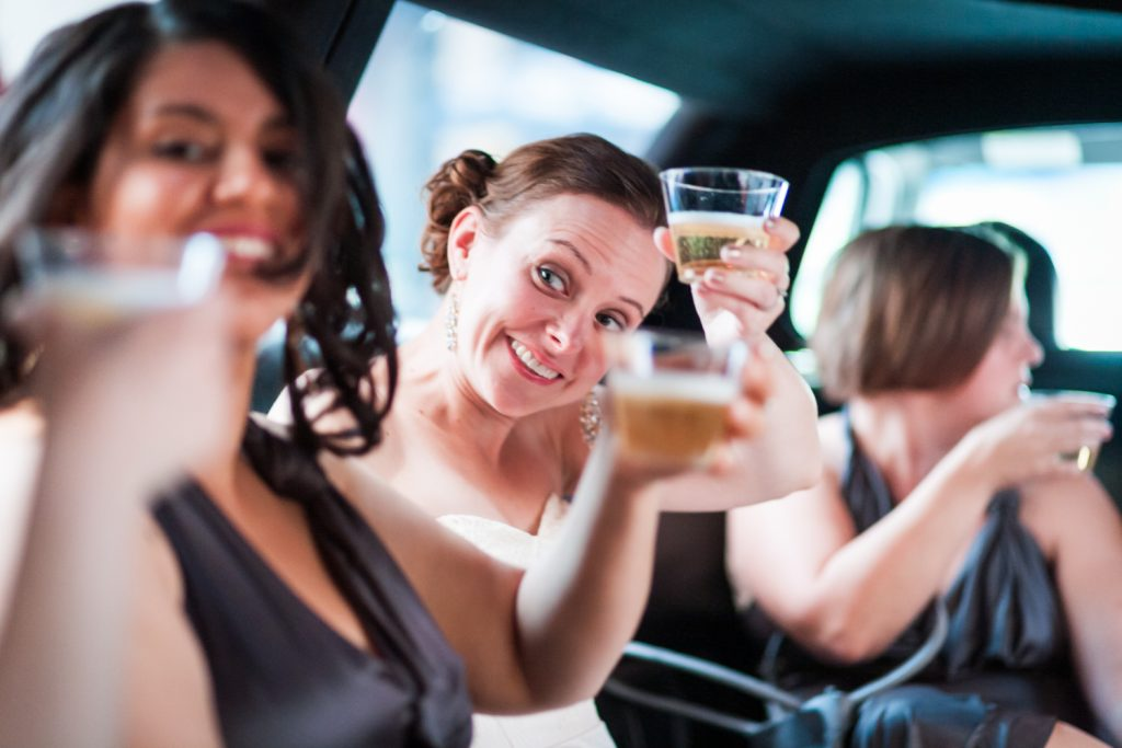 Bride raising glass of champagne in backseat of limo