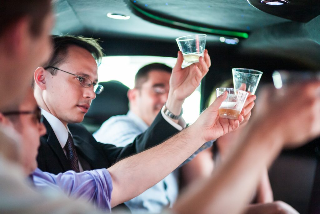 Groom raising plastic glass in back of limo