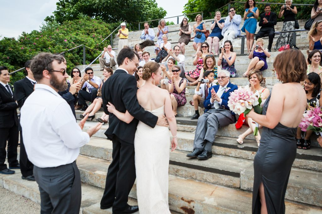 Bride and groom hugging in front of crowd at a Brooklyn Bridge Park wedding