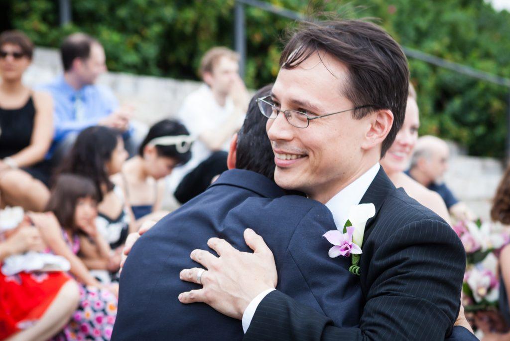 Groom hugging guest at a Brooklyn Bridge Park wedding