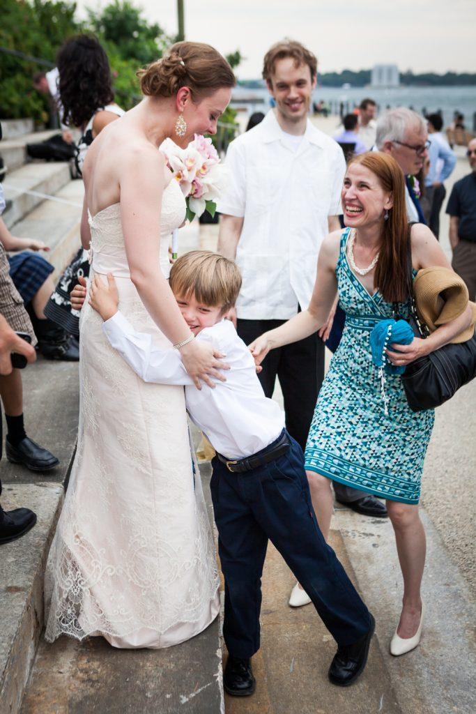 Little boy hugging bride at a Brooklyn Bridge Park wedding
