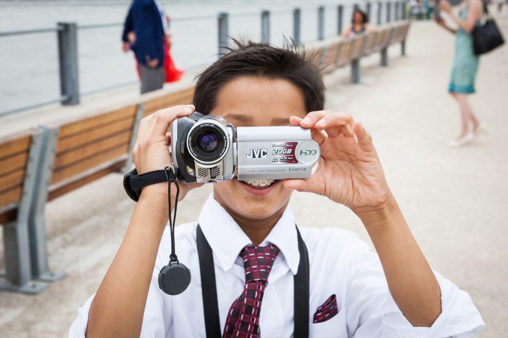 Young boy using video camera at a Brooklyn Bridge Park wedding