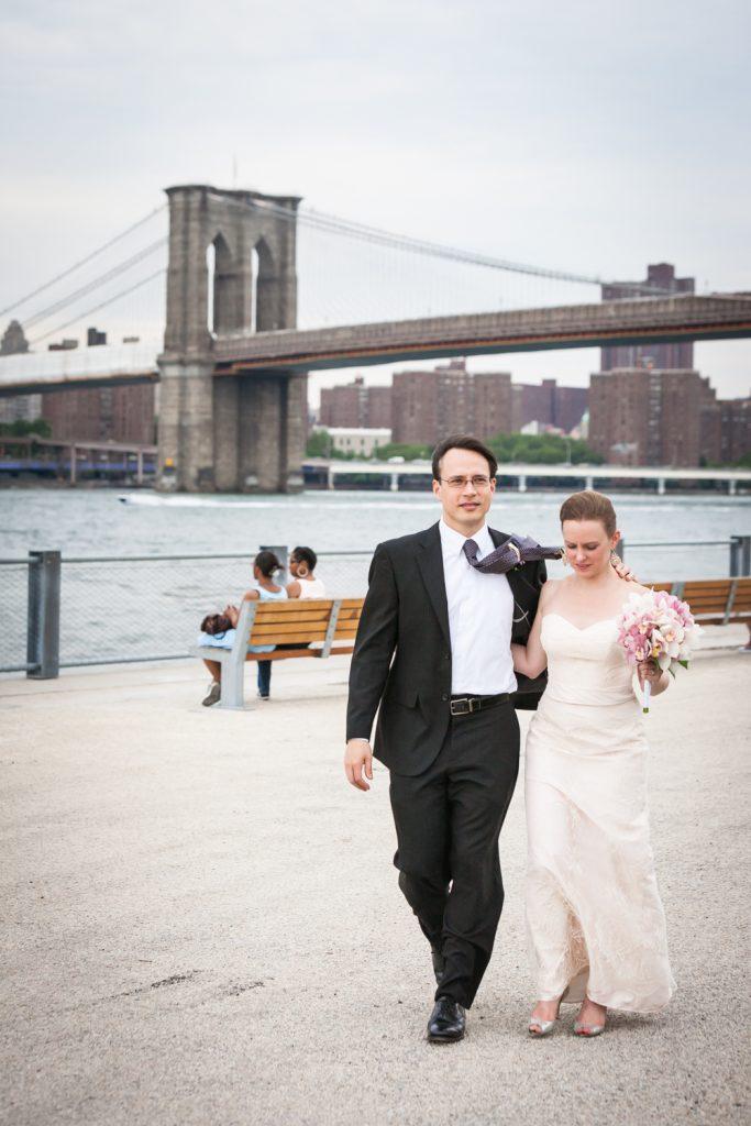 Bride and groom walking with Brooklyn Bridge in background at a Brooklyn Bridge Park wedding