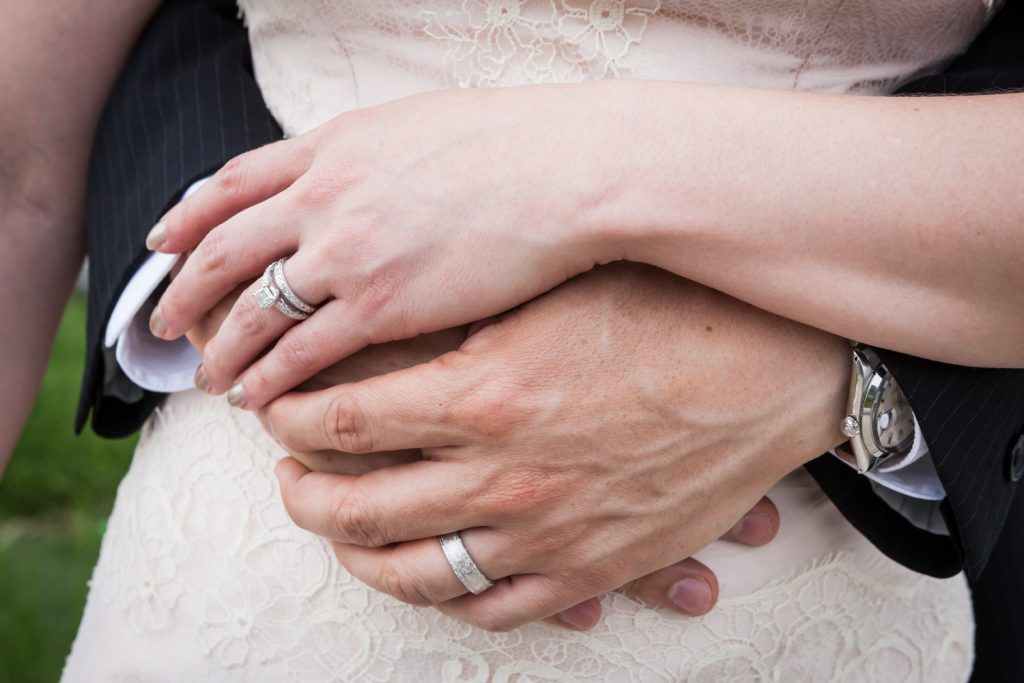 Close up on bride and groom clasping hands and wearing wedding rings