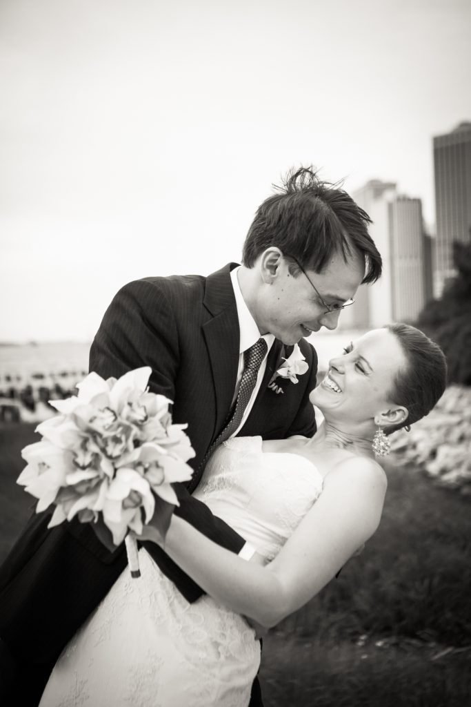 Black and white photo of groom dipping bride in Brooklyn Bridge Park