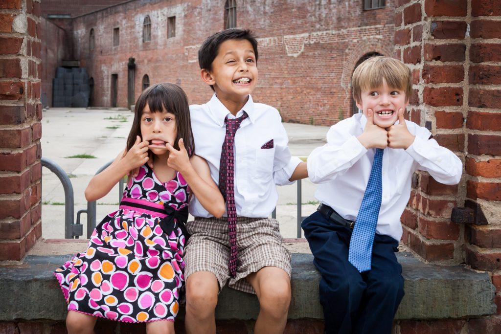 Three kids sitting on brick wall making funny faces at a Brooklyn Bridge Park wedding