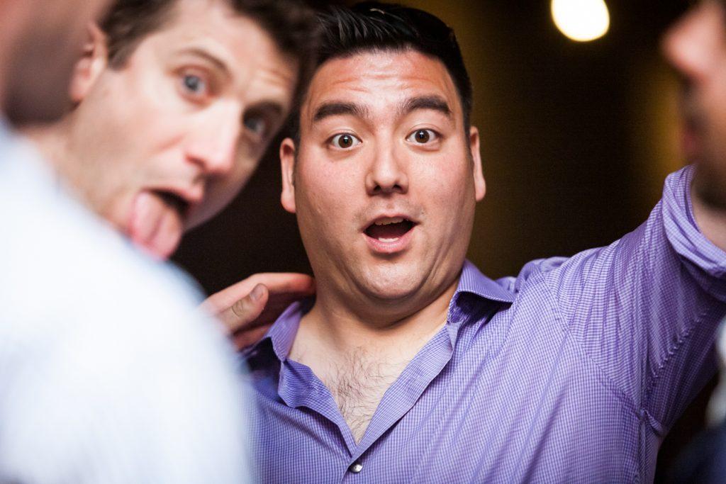 Two men clowning around during Williamsburg wedding reception