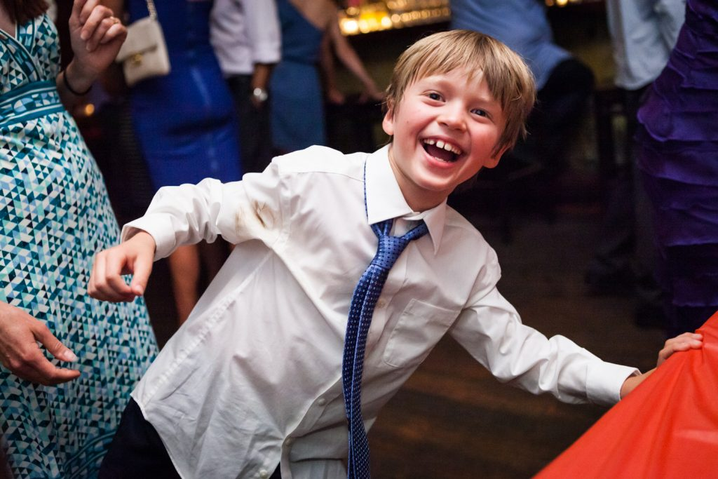 Young boy clowning around and wearing blue tie during Williamsburg wedding reception