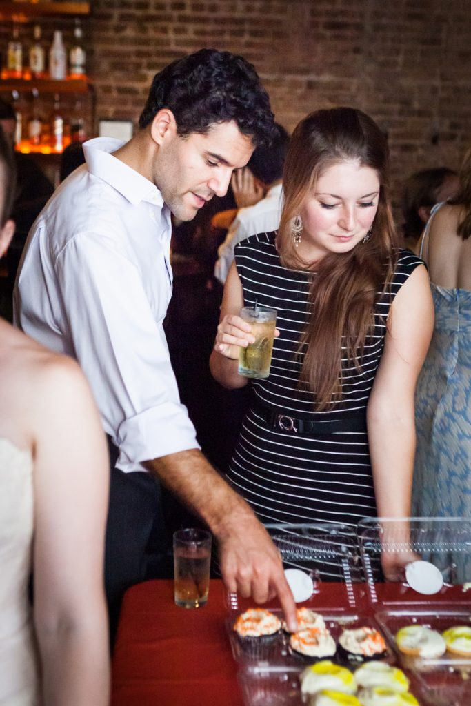 Couple choosing cupcakes during Williamsburg wedding reception
