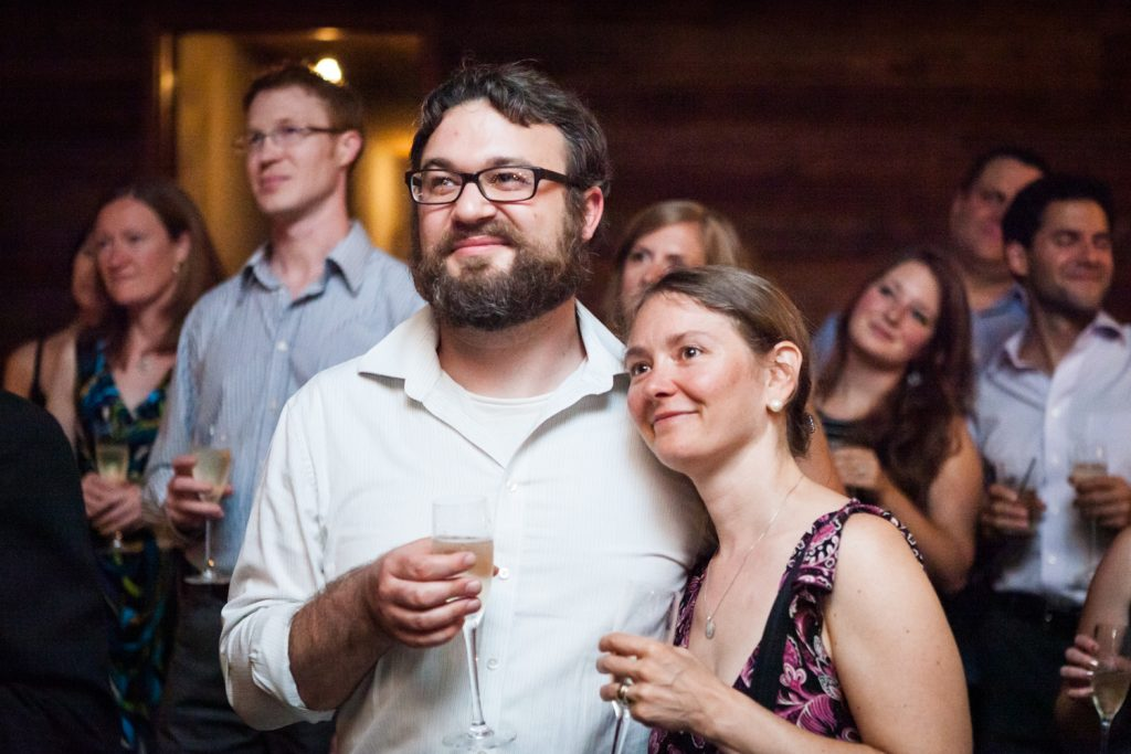 Couple holding glasses and listening to speeches during Williamsburg wedding reception