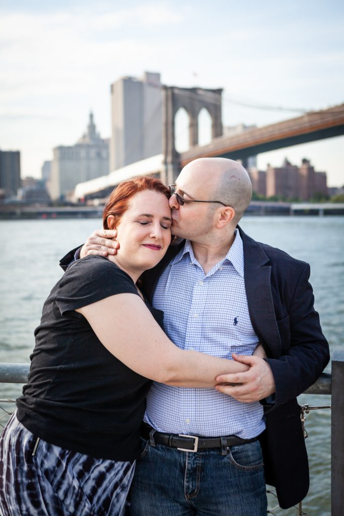 Man kissing woman on cheek with Brooklyn Bridge in background during a Brooklyn Bridge Park engagement portrait session