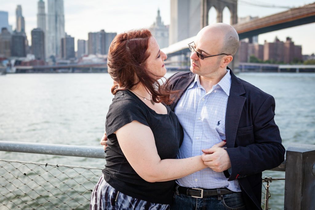 Couple hugging with Brooklyn Bridge in background during a Brooklyn Bridge Park engagement portrait session