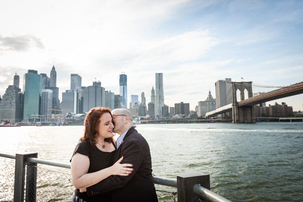 Man kissing woman on cheek with NYC skyline in background during a Brooklyn Bridge Park engagement portrait session