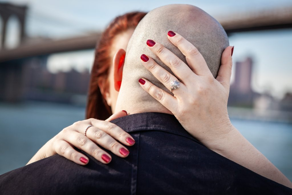 Close up of woman's hand wearing engagement ring on the back of man's bald head