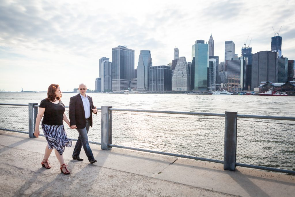 Couple walking on pathway with NYC skyline in background during a Brooklyn Bridge Park engagement portrait session