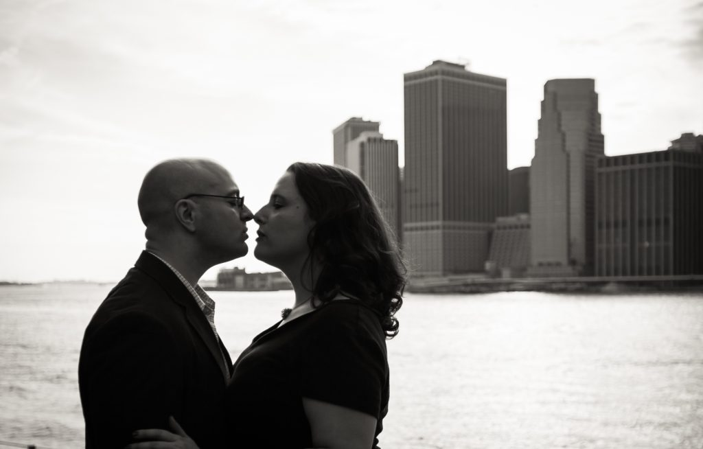 Black and white photo backlit couple with NYC skyline in background